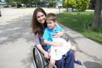 A mother and son, sit outside in a driveway facing forward. Both are smiling. The mother is a wheelchair user.