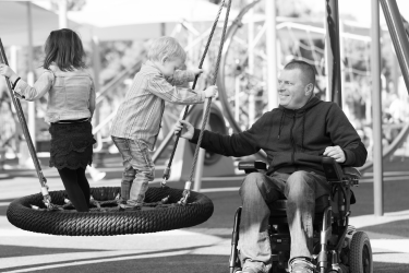 A father, who uses an electric wheelchair, sits next to a park swing with a young boy standing on the swing to his side. He is smiling. The man's hand is outstretched, barely gripping the support cable as he moves the swing in a back and forth motion to the delight of the child.