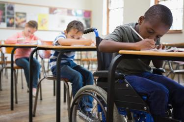 A young African-American boy in a blue and black wheelchair sits behind his classroom desk and works on an assignment with a pencil. Behind him are a boy and girl in their desks, also writing at their desks.