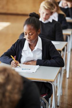 The photo depicts a row of students, all wearing a school uniform of a white button-up shirt and black sweater, sitting at their desks taking a test. In focus in the photo is an African-American female student with her hair pulled back, holding a yellow mechanical pencil and marking her test paper in front of her on the desk.